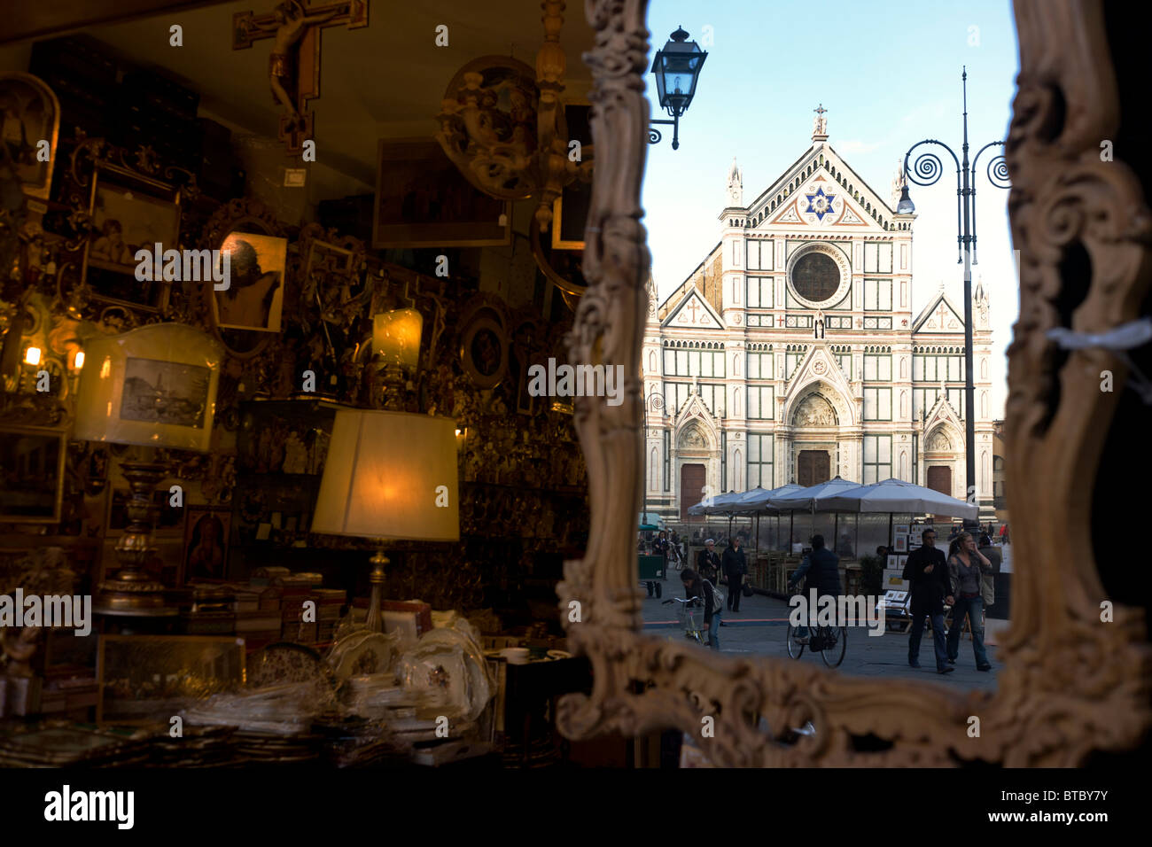 Religious icons and souvenirs with Santa Croce church reflected in mirror at end of Piazza. - Stock Image