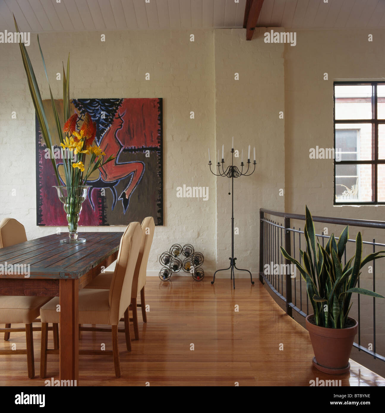 Vase Of Tall Flowers On Table In Modern Dining Room With Wooden Floor And  Cactus And Large Abstract Painting On Wall