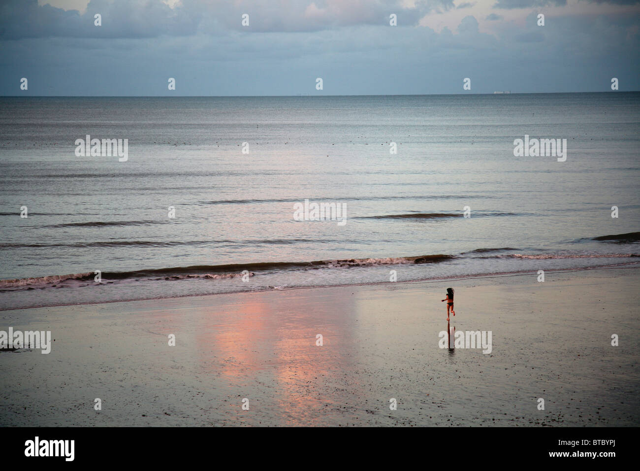The sea at Hastings, East Sussex with a lone figure running toward the waters' edge. Stock Photo