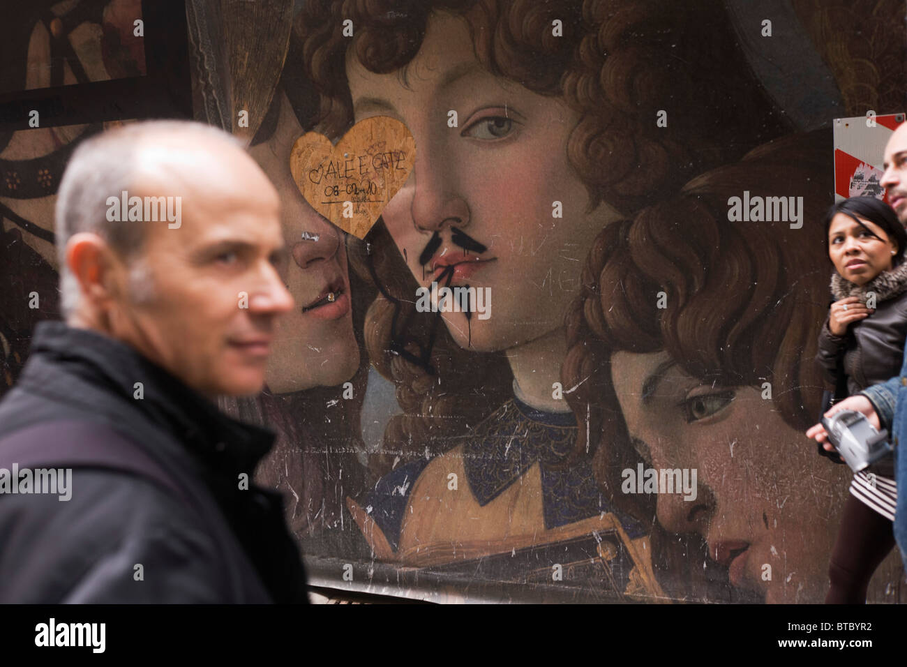 Tourists pass-by renaissance paintings on construction hoarding in Florence's Piazza degli Uffizi. - Stock Image