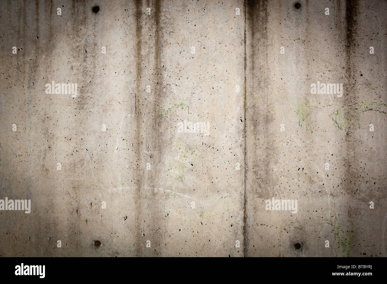 Tall concrete wall in rough, gunge style with stains and wear - Stock Image
