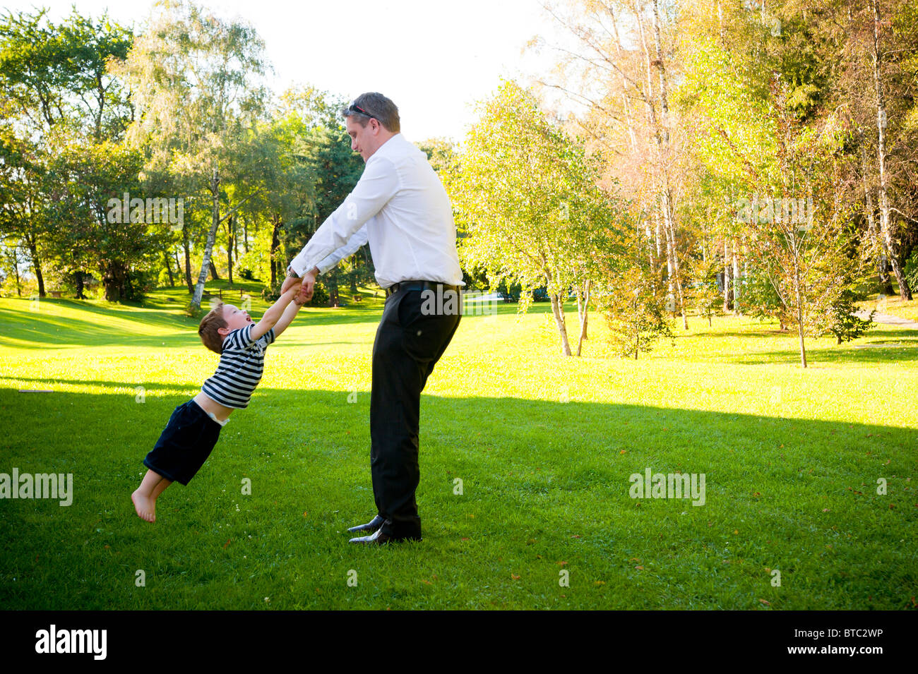 Man spinning around a little boy - Stock Image