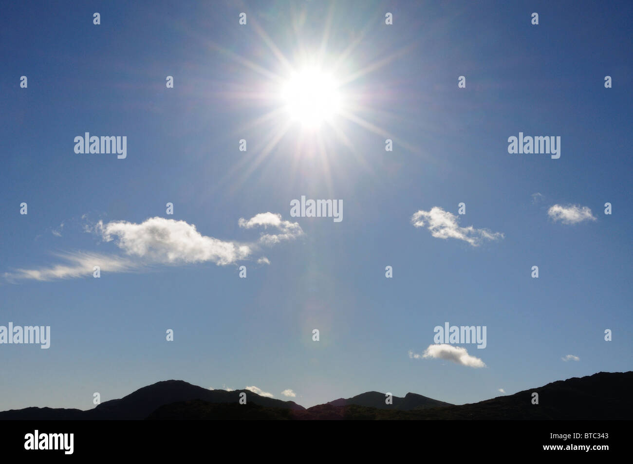 Starburst sun over mountains in the English Lake District - Stock Image