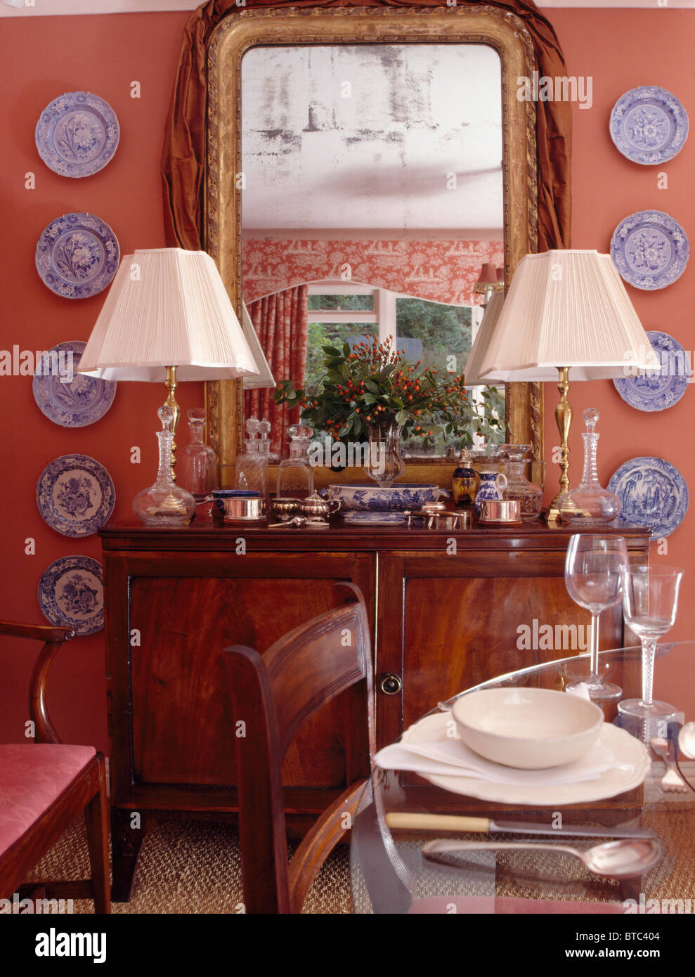 Mirror Above Cream Lamps On Antique Sideboard In Pink Dining Room With Blue White Plate Collection Wall