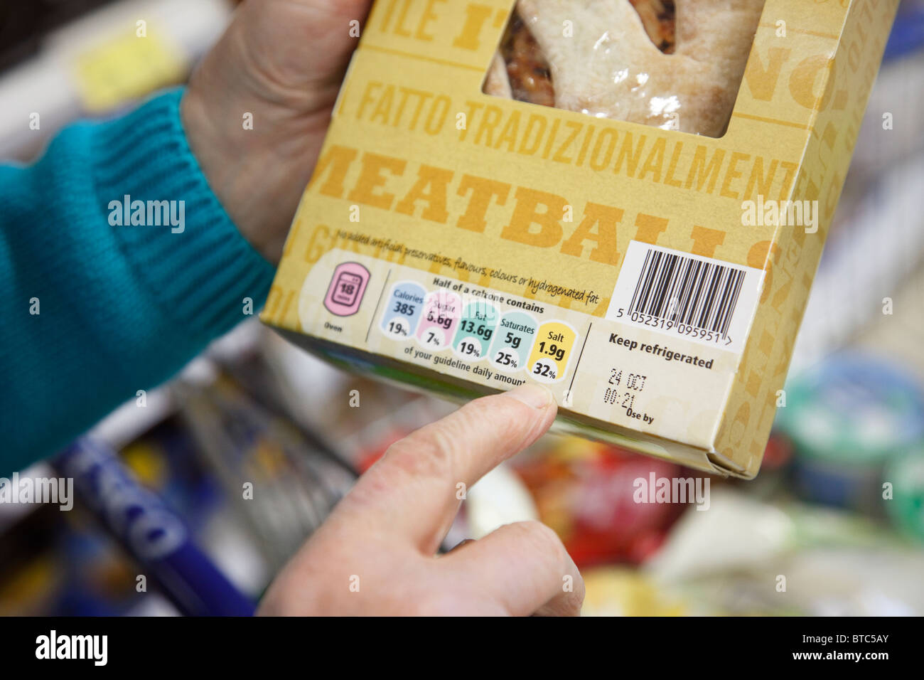 UK, Europe. Senior woman checking the food labels for salt content on a Calzone packet. - Stock Image