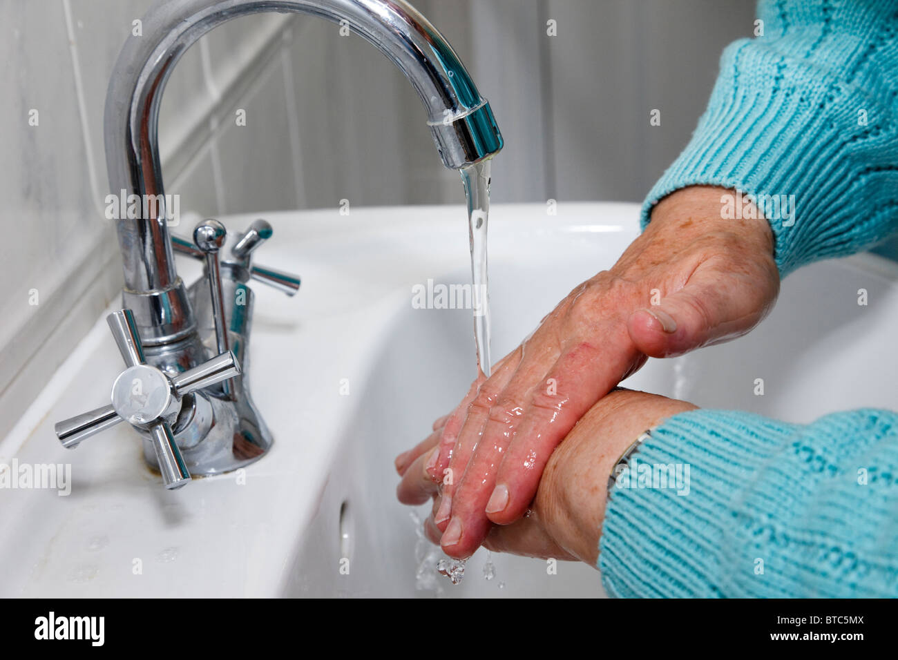Senior woman washing hands with tap water running into a handbasin. - Stock Image