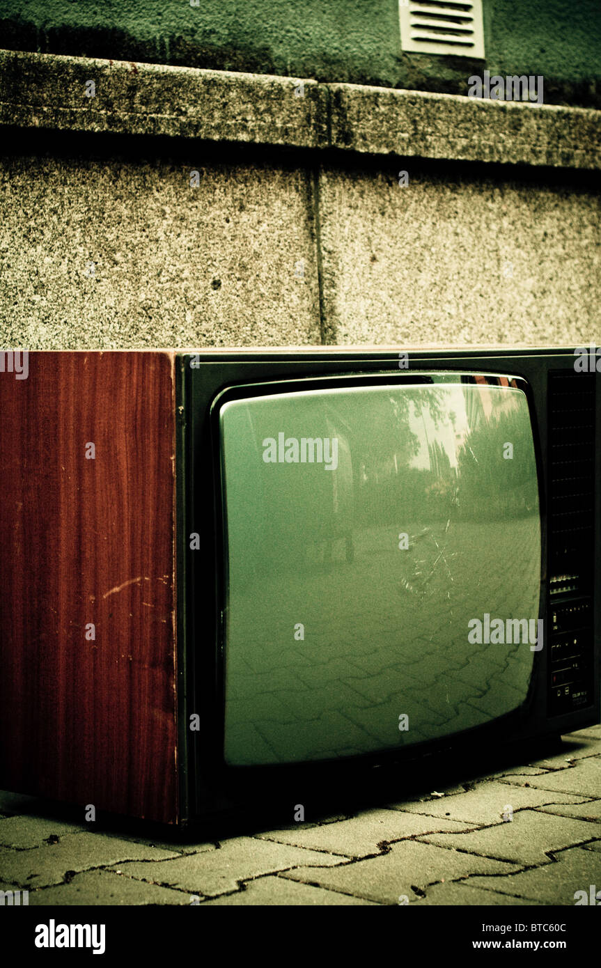 old analogue television abandoned on street - Stock Image