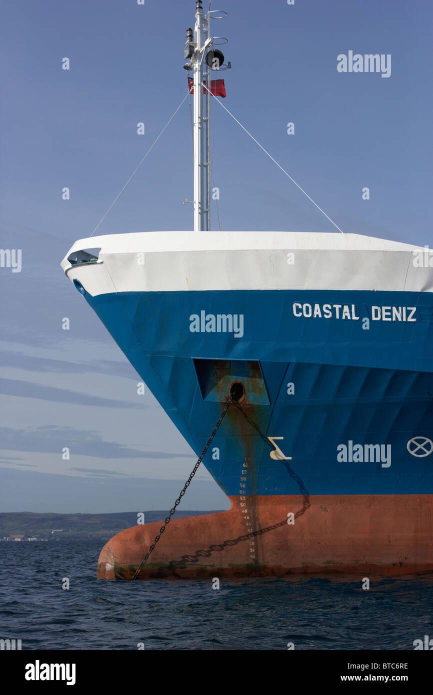 bulbous bow of coastal deniz dry cargo hazard a major ship at anchor in coastal waters of the uk - Stock Image