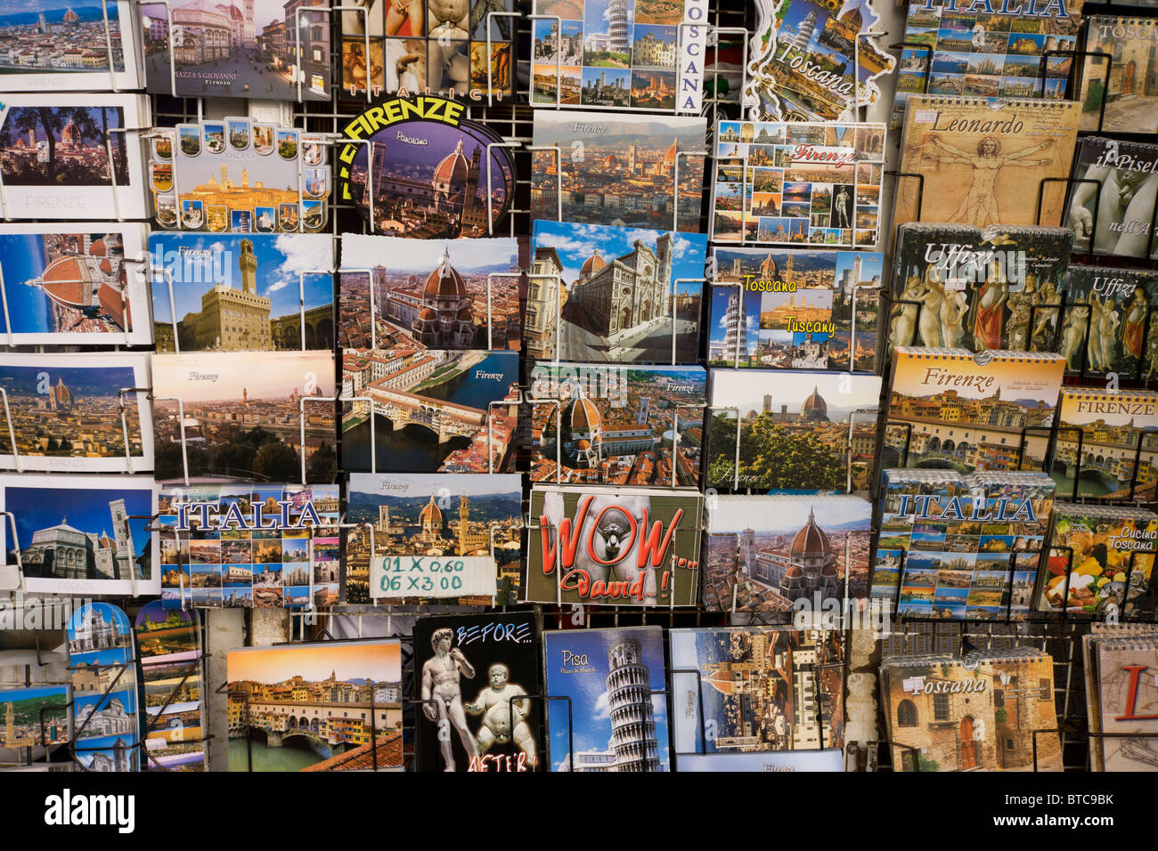Florence postcards on rack in Piazza Santa Giovanni beneath Florence's Santa Maria del Fiore (Duomo) Cathedral. - Stock Image