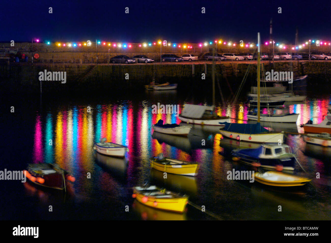 Night shot of Mousehole, Cornwall harbour lights. Slight amount of noise and motion blur due to long exposure required. - Stock Image