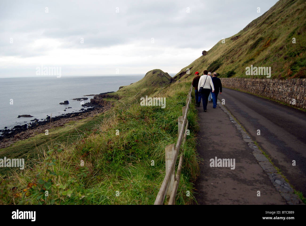 Walkers on road near the Giants Causeway, County Antrim, Northern Ireland - Stock Image