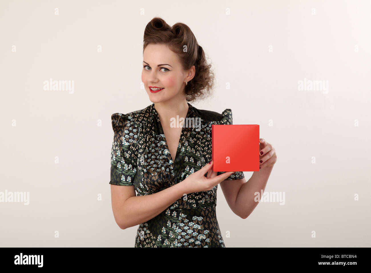 Retro housewife holding a red carton - Stock Image