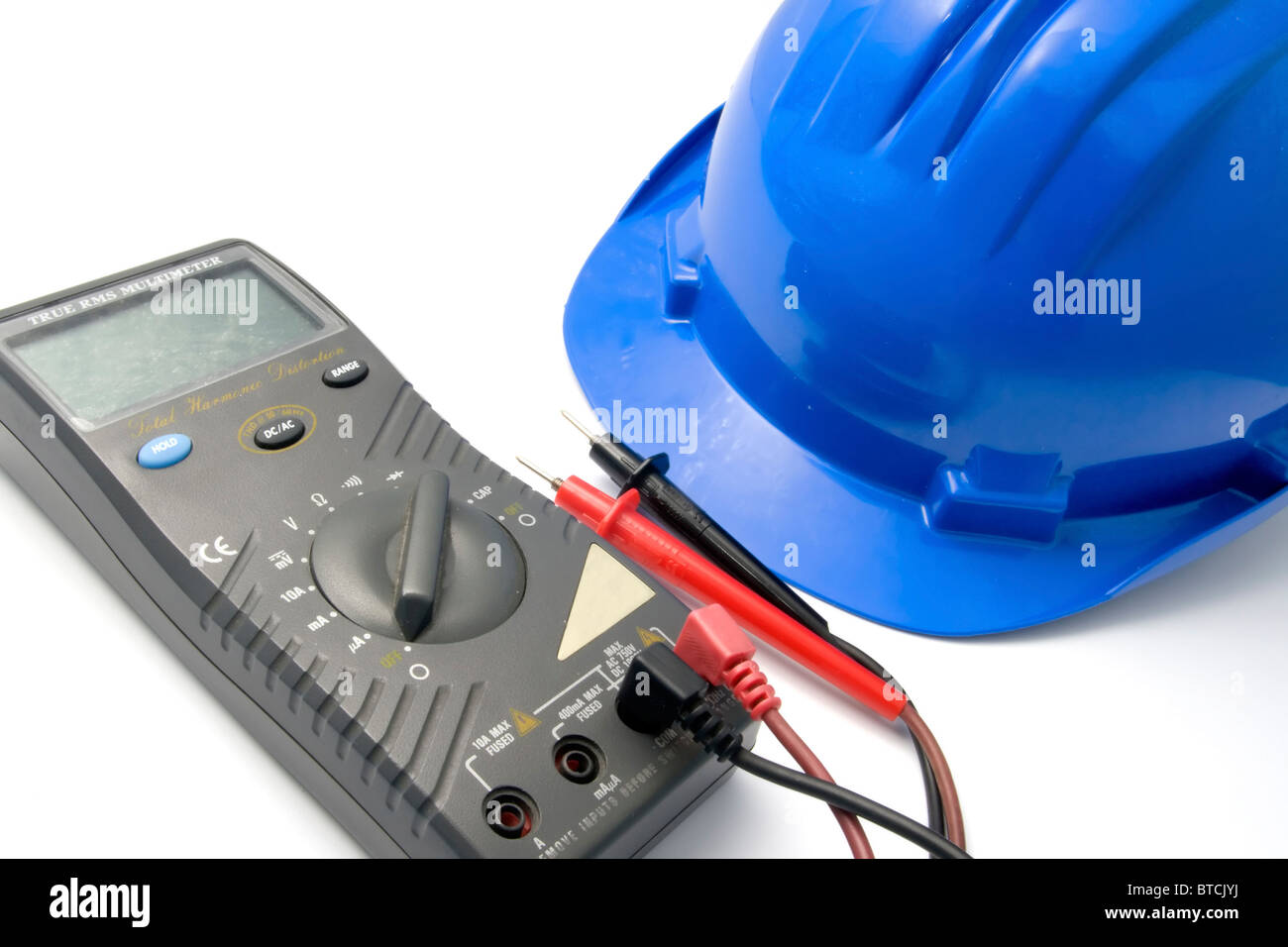 Isolated blue helmet and multimeter for workers - Stock Image