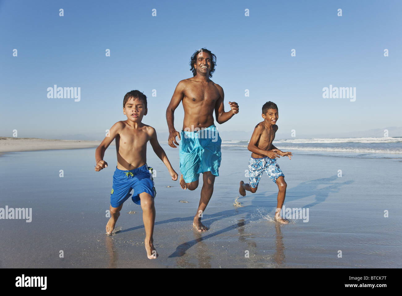 Young Indian man and boy's running along waters edge. - Stock Image