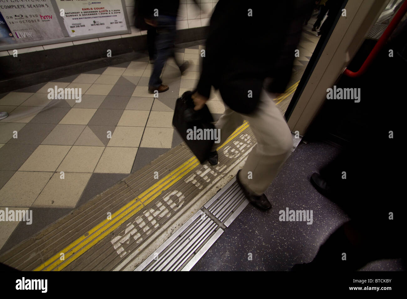 Passenger stepping onto london underground train on the tube network, with mind the gap sign on platform - Stock Image
