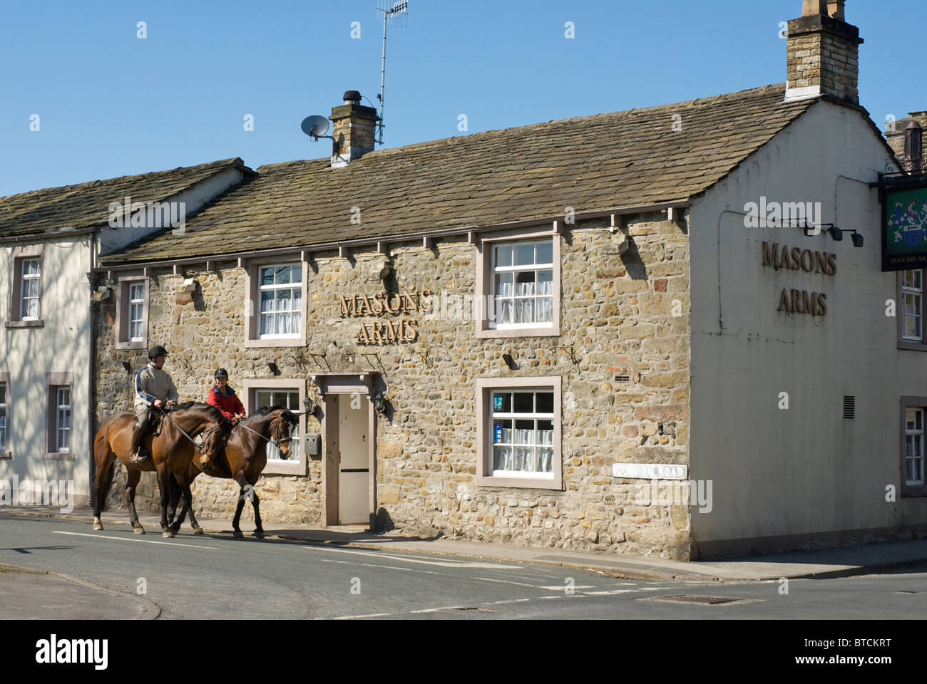 Two horse riders passing the Masons Arms pub in the village of Gargrave, North Yorkshire, England UK - Stock Image