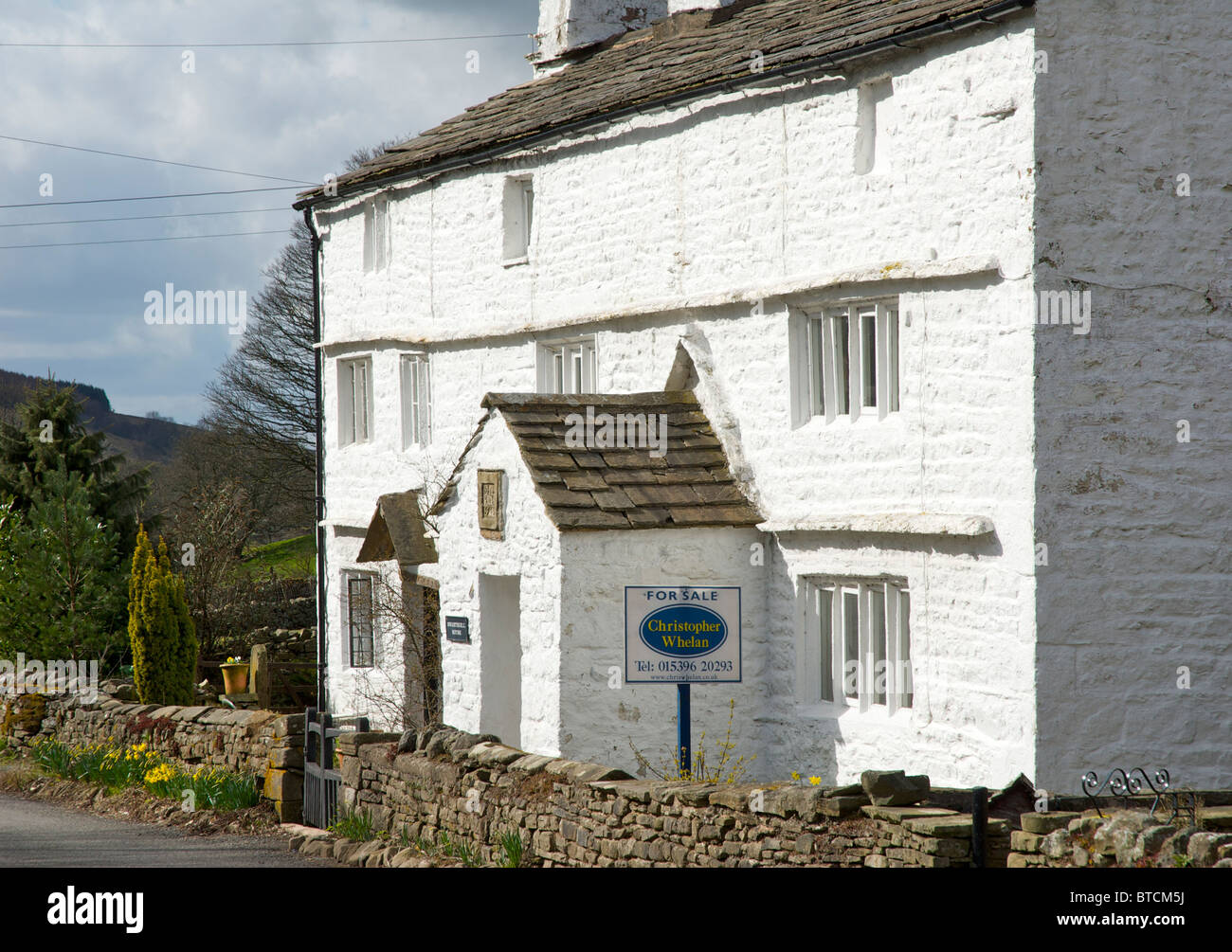 Whitewashed cottage for sale in Garsdale, Yorkshire Dales National Park, England UK, with a datestone of 1746 above - Stock Image