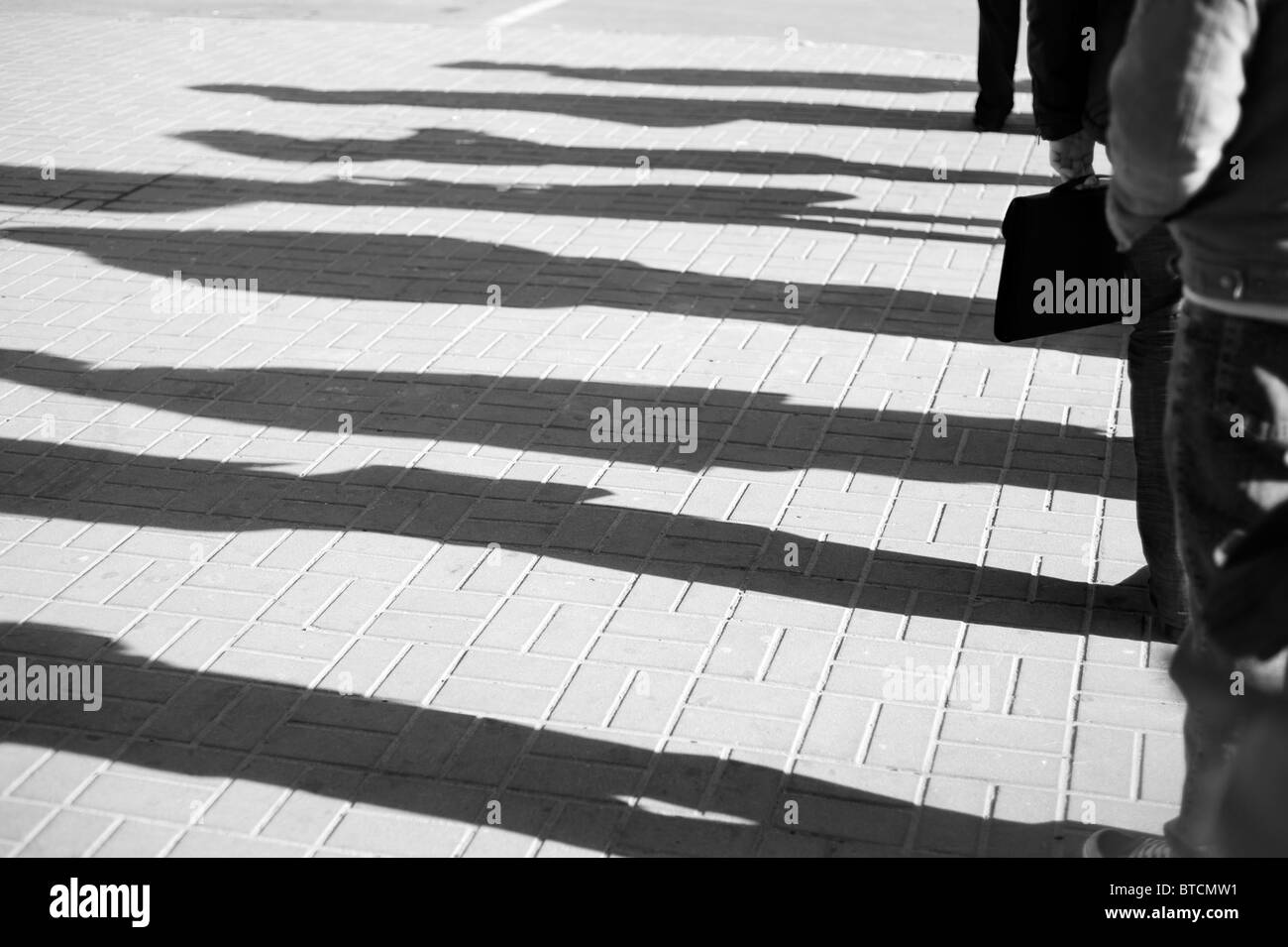 Shadow of a people standing in a queue - Stock Image