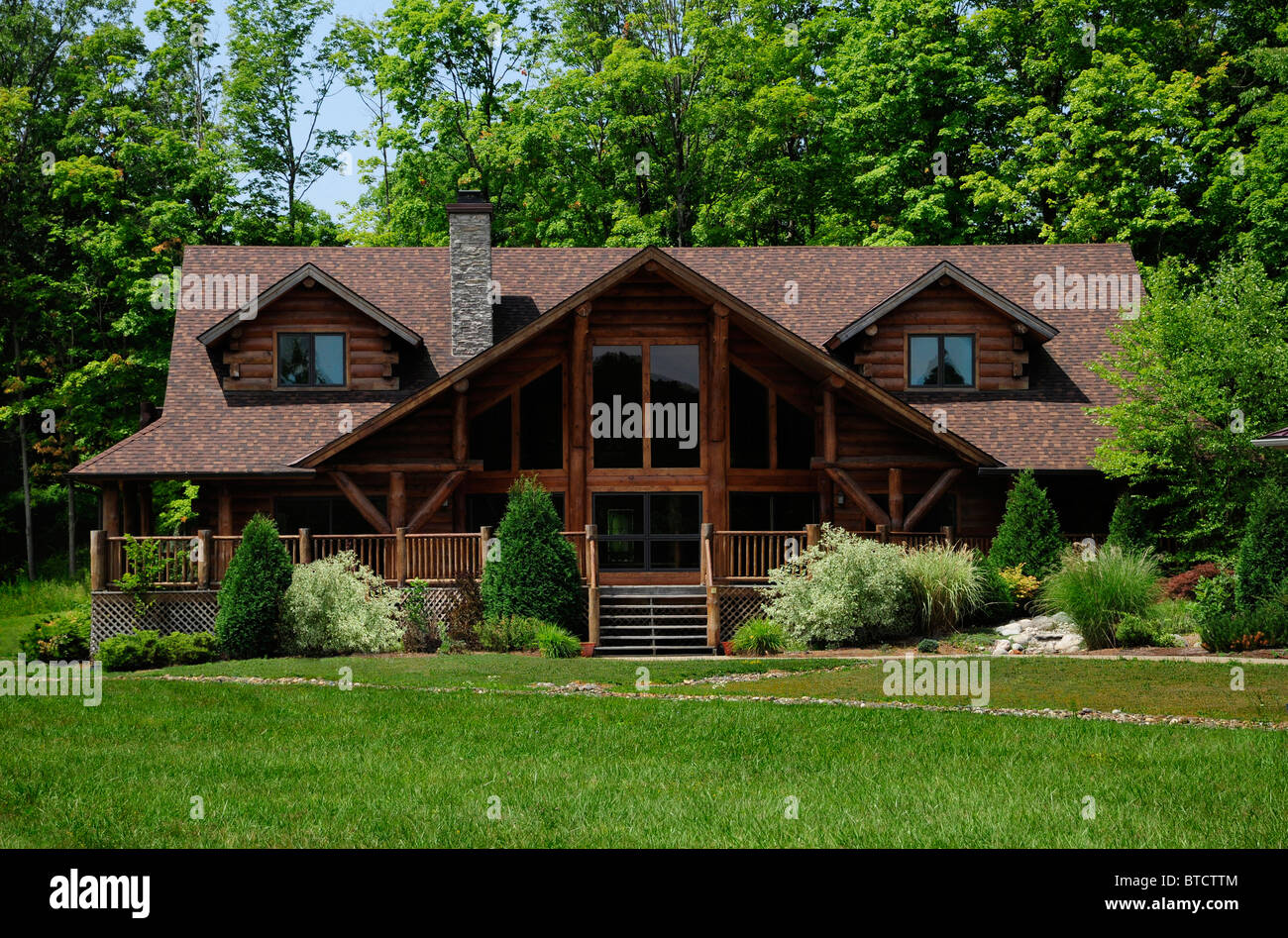 Large model log cabin in wooded area - Stock Image