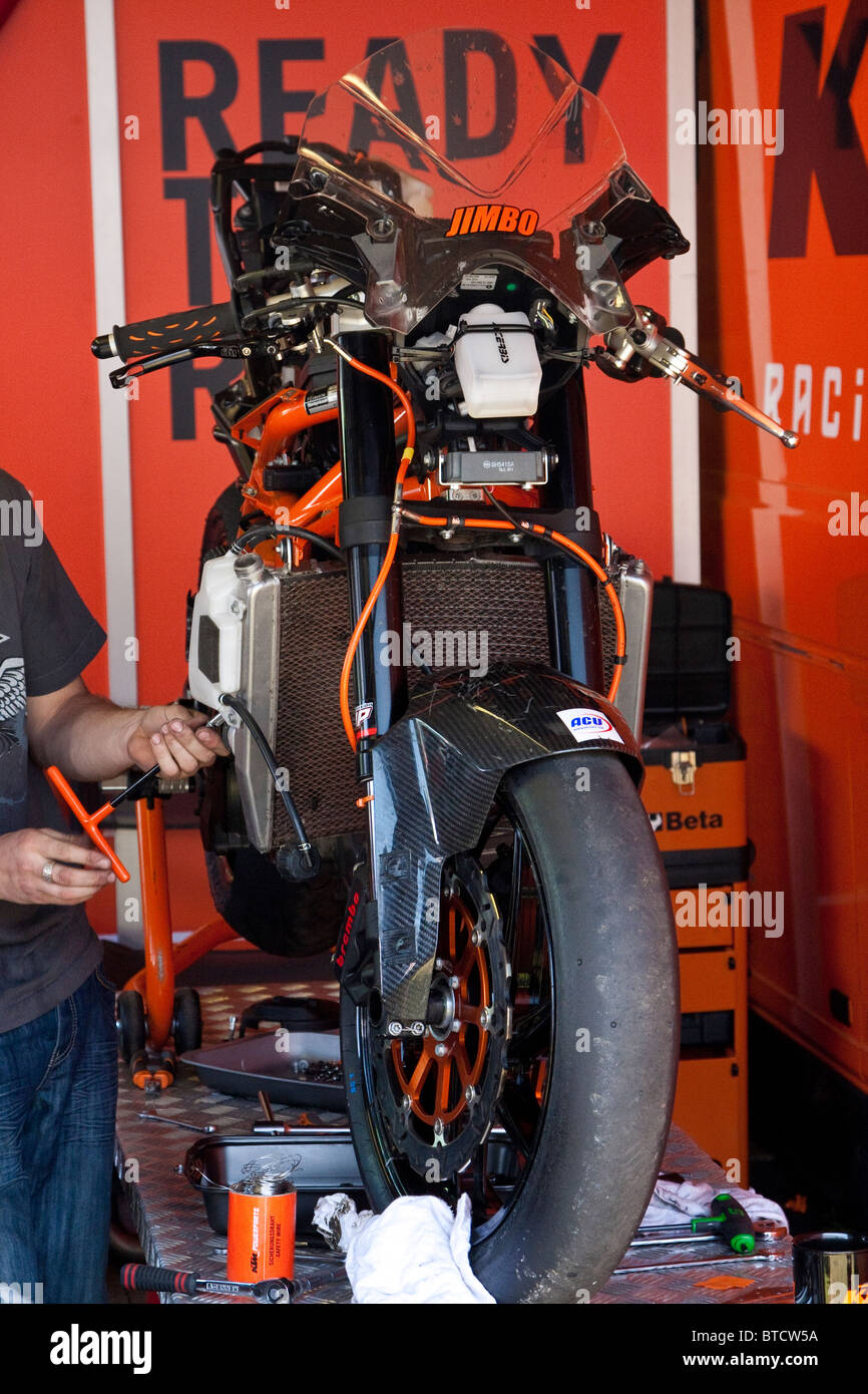 2010 TT KTM racing bike being built in the pit garage.  The fairing is not in place but the wheels, fork and engine - Stock Image