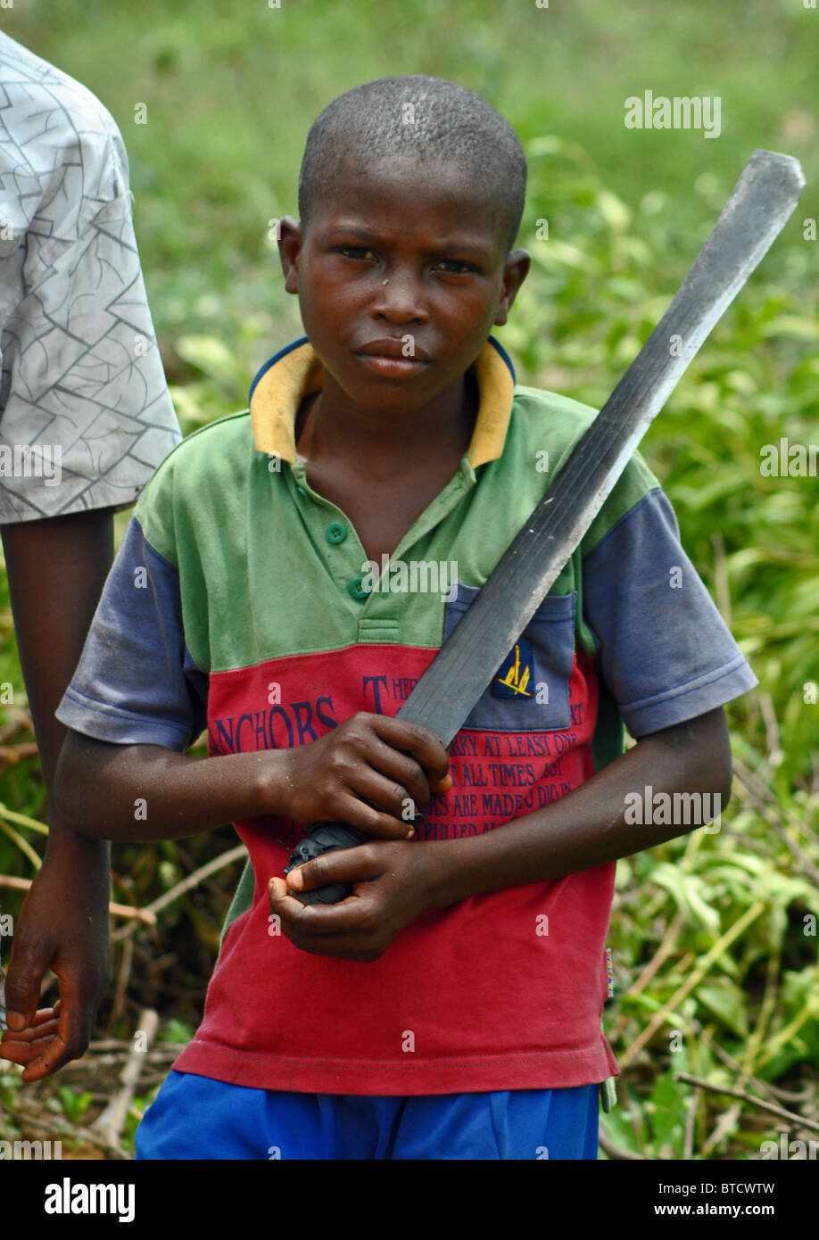 Young child with machete, for felling trees in Western Ivory Coast, West Africa - Stock Image