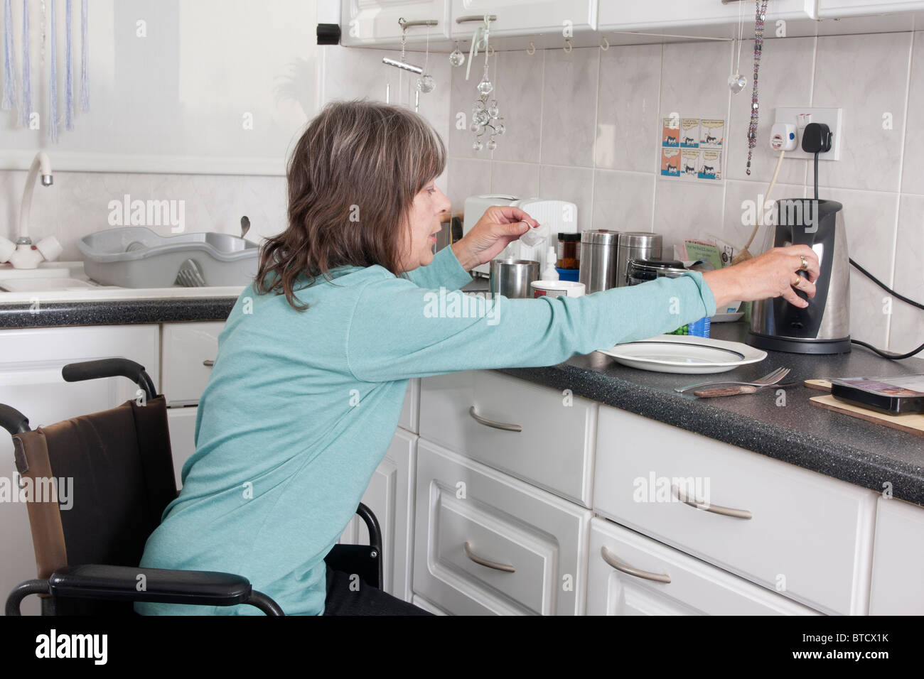 disabled woman in wheelchair preparing food in kitchen Stock Photo ...