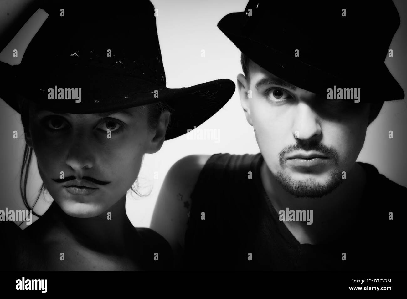 portrait of young man and woman with mustache wearing hats - Stock Image