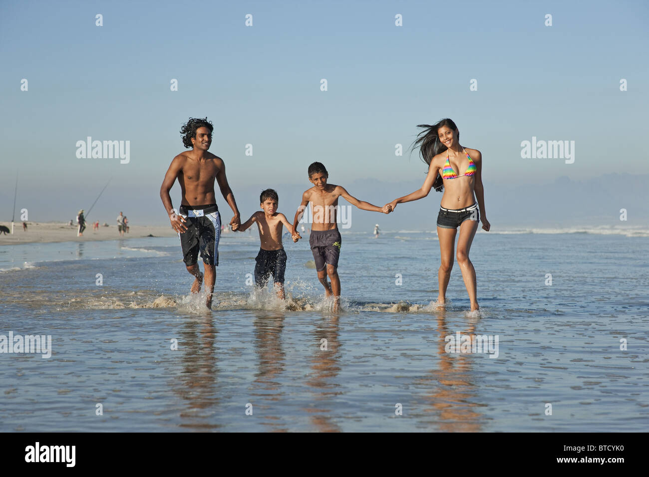 Indian family, dressed in swim wear, playing in shallow waves. - Stock Image