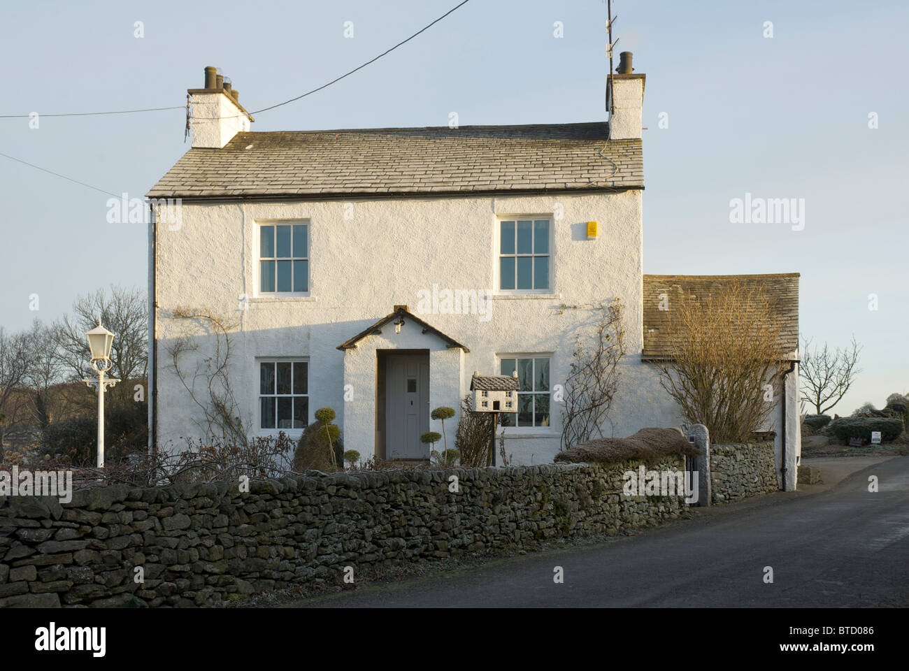 House in the village of Preston Patrick, near Kendal Cumbria, England UK, with birdhouse in a similar style - Stock Image