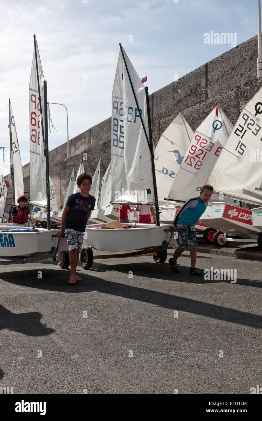 Getting ready to take part in a regatta of Optimist sailing dinghies in Playa San Juan Tenerife Canary Islands Spain - Stock Image