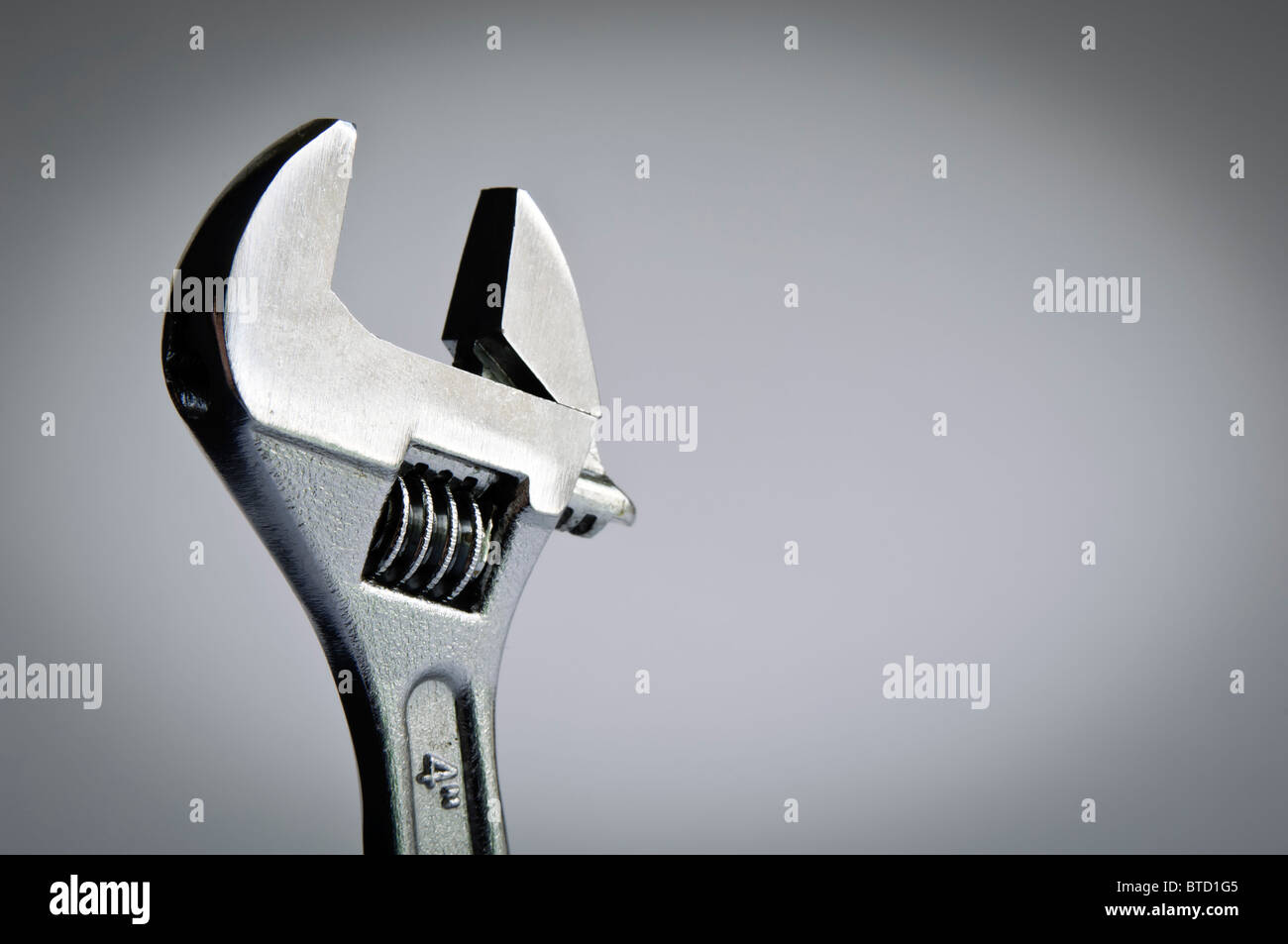 Spanner / wrench head against a grey background with copy space - Stock Image