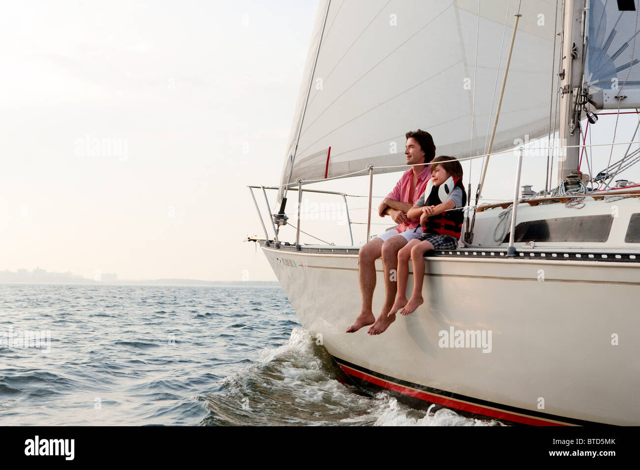 Father and son sitting on yacht - Stock Image