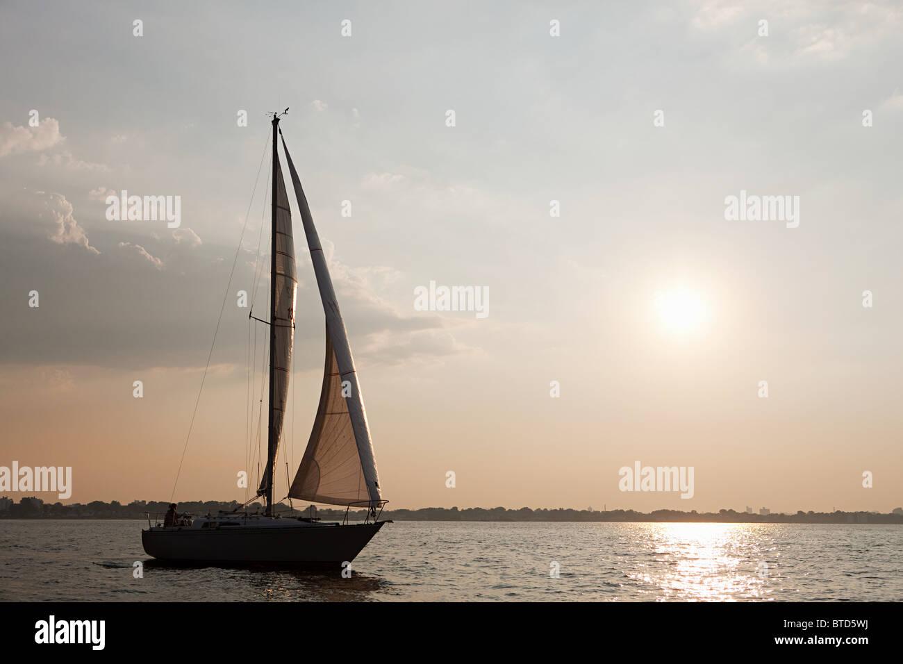 Yacht sailing on sea at dusk - Stock Image