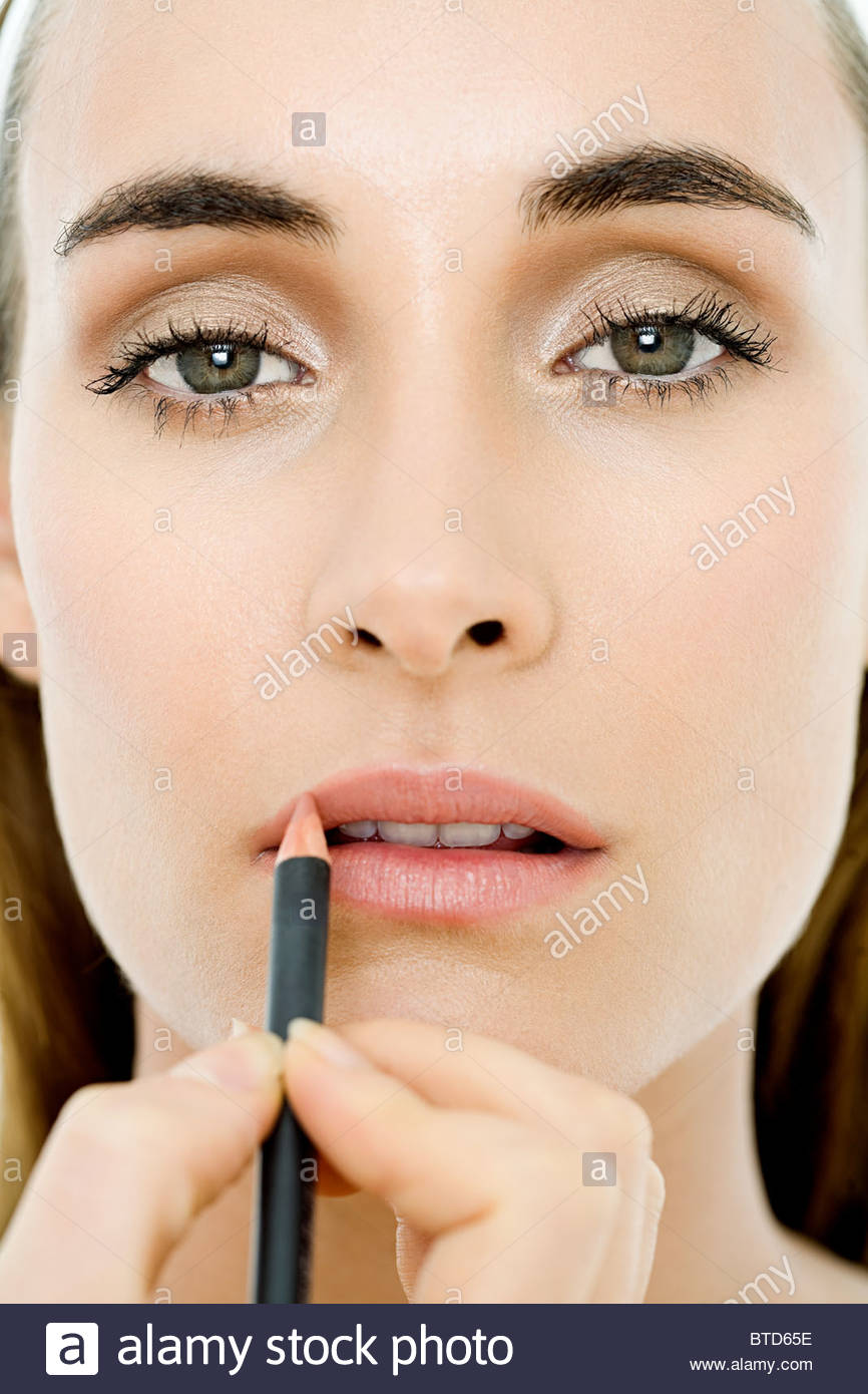 Young woman applying lip liner - Stock Image
