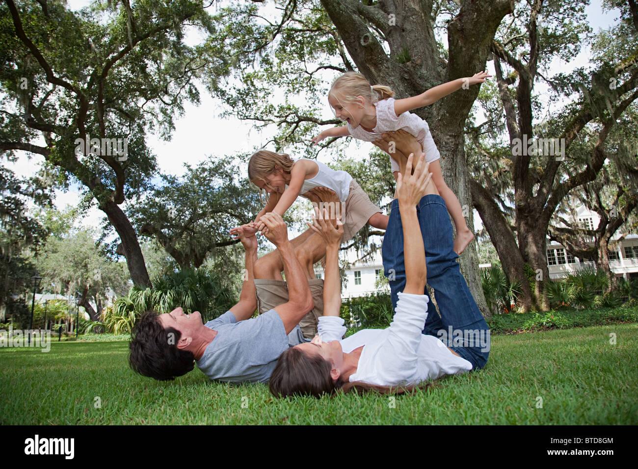 Girls balancing on feet of parents - Stock Image