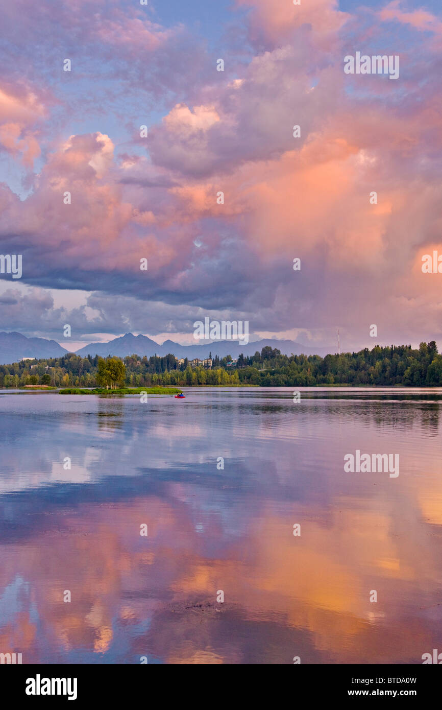 Couple kayaking in Westchester Lagoon at with pink clouds reflecting in the water at sunset, Downtown Anchorage, - Stock Image