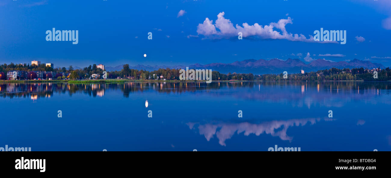 Twilight view of full moon over Westchester Lagoon in downtown Anchorage, Southcentral Alaska, Fall - Stock Image