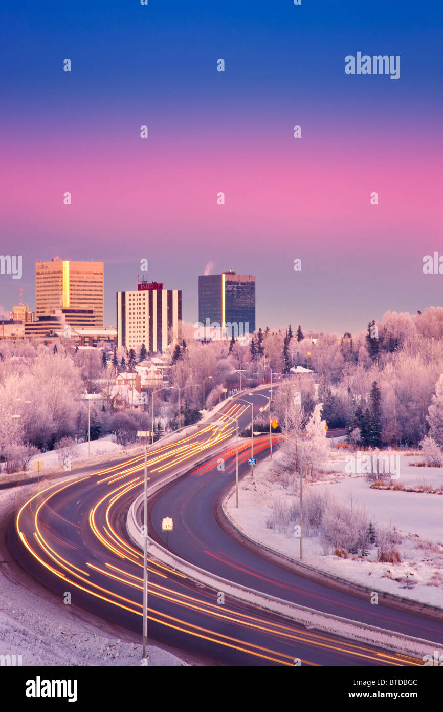 Sunset view of traffic on Minnesota Blvd. with downtown Anchorage in the background, Southcentral Alaska, Winter/n - Stock Image