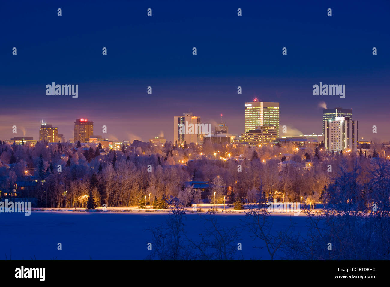 Skyline view of downtown Anchorage and Westchester Lagoon at twilight, Southcentral Alaska, Winter Stock Photo
