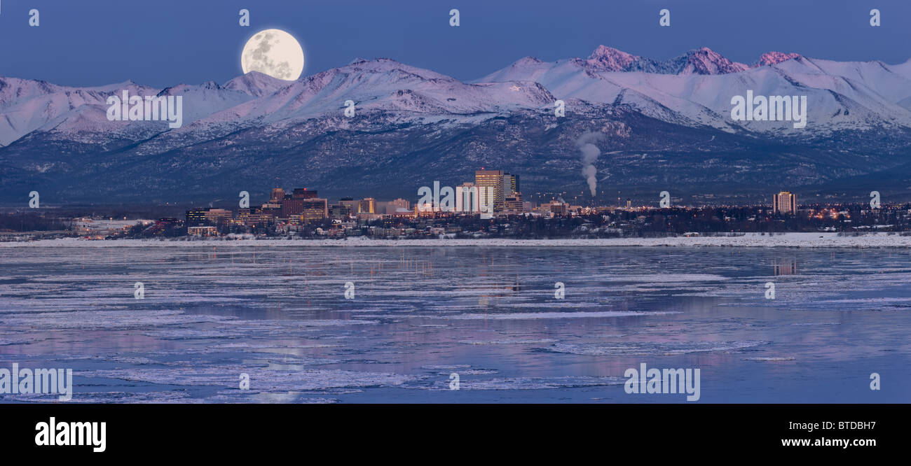 Panoramic of moon rising over the Anchorage skyline and Chugach Mountains at dusk with  fireworks overhead, Alaska, - Stock Image