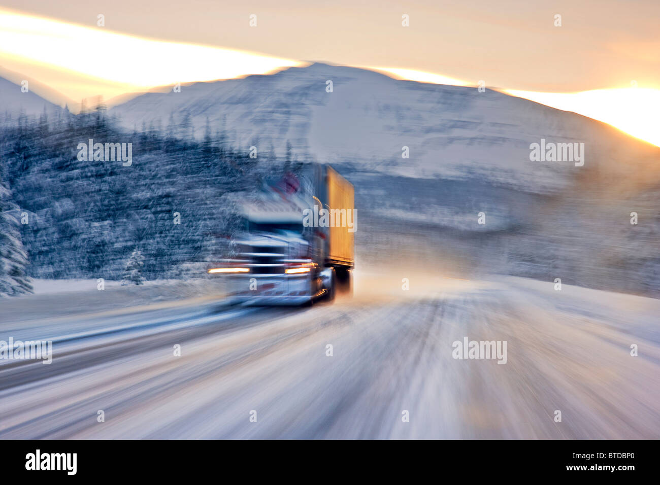 Semi truck driving on the snowcovered Seward Highway at sunrise, Southcentral Alaska, Winter Stock Photo