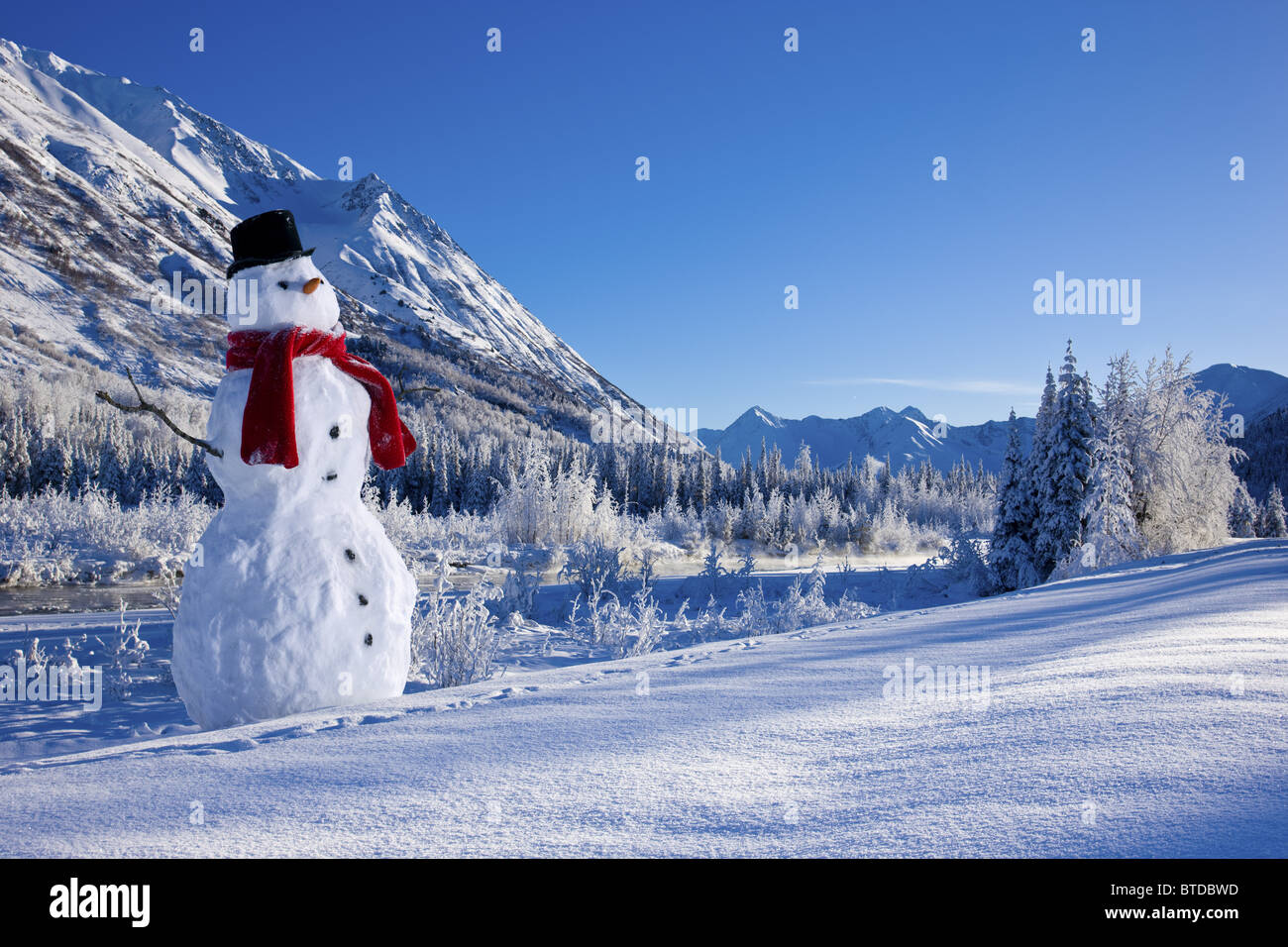 Snowman with a top hat and scarf in the Chugach Mountains,/nSouthcentral Alaska, Winter, COMPOSITE - Stock Image