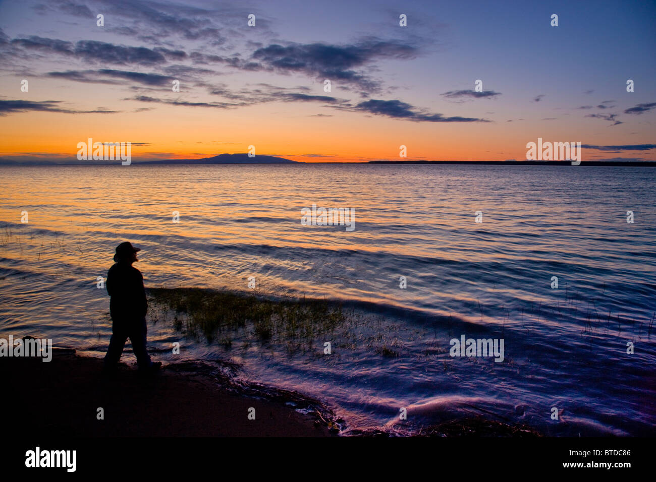 Silhouette of a man standing on the shore of Knik Arm while watching  the sunset over Mount Susitna, Alaska, Summer - Stock Image