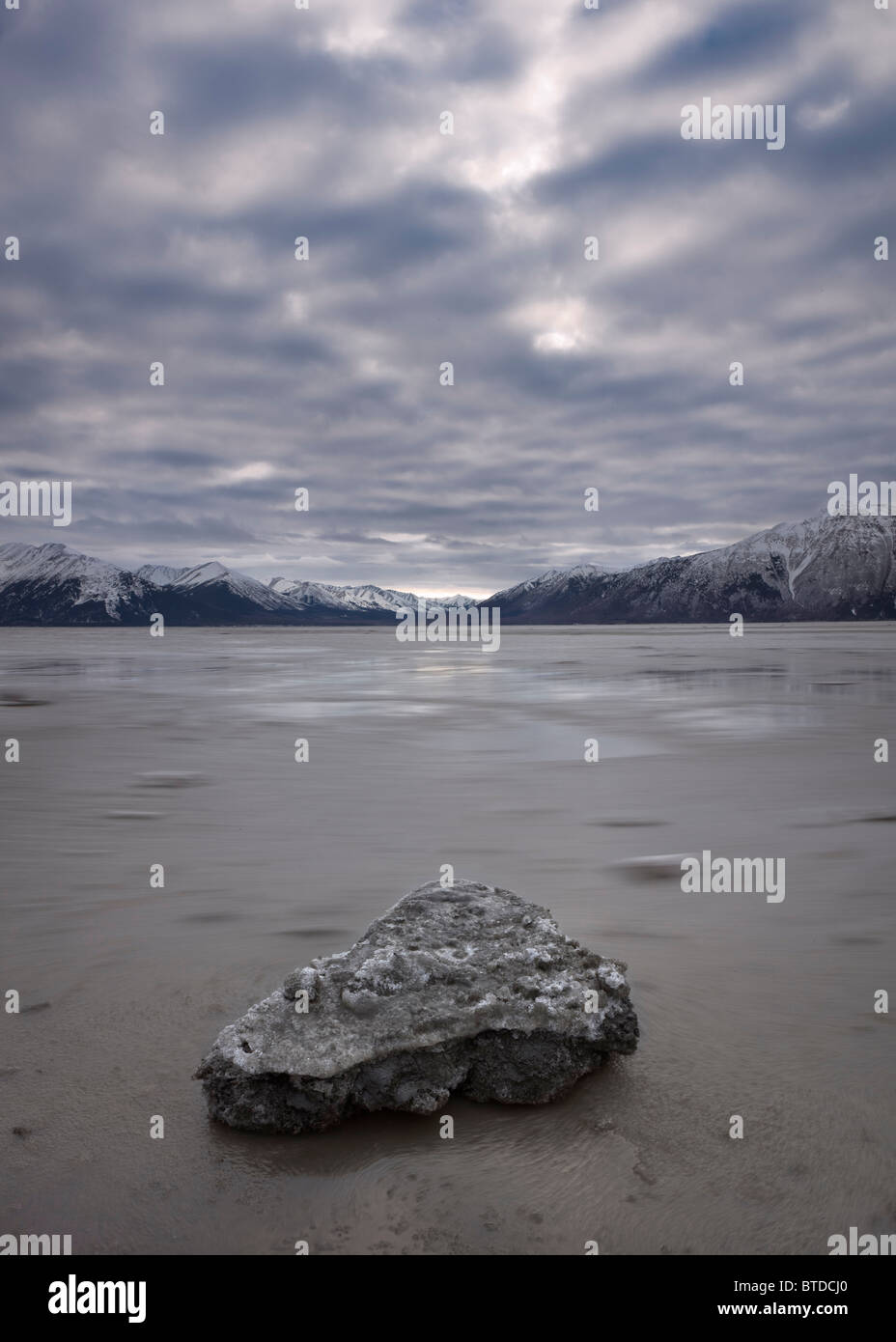 Stranded ice chunks at low tide on the Turnagain Arm under low overcast skies, Southcentral Alaska, Winter - Stock Image
