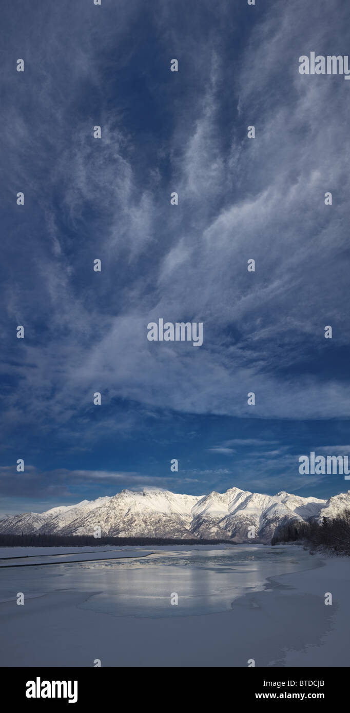 Cirrus clouds over the icy Knik River and Talkeetna Mountains in Knik River Valley, Matanuska Susitna Valley, Alaska - Stock Image