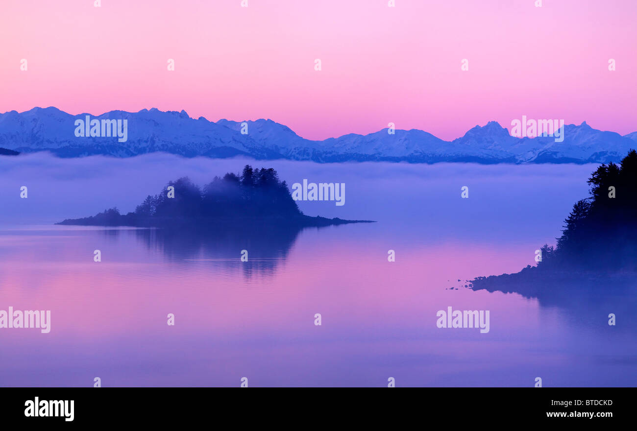 Foggy and pink sunset over the Chilkat Mountains and Favorite Passage near Juneau, Inside Passage, Southeast Alaska, - Stock Image