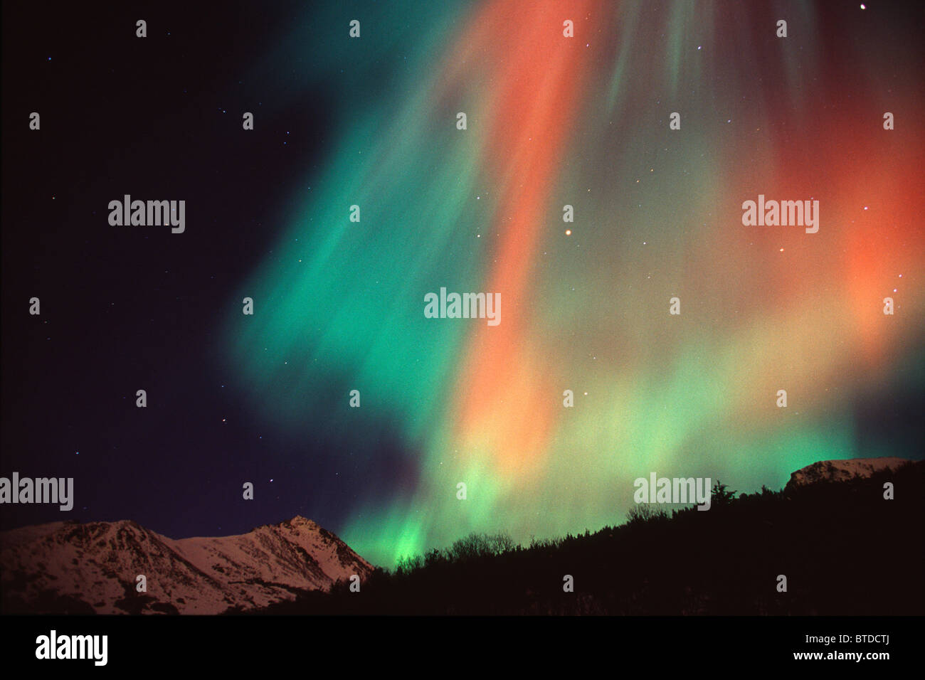 Multi colored Northern Lghts fill the night sky and cast colored shadows on the mountain tops of Chugach State Park, - Stock Image