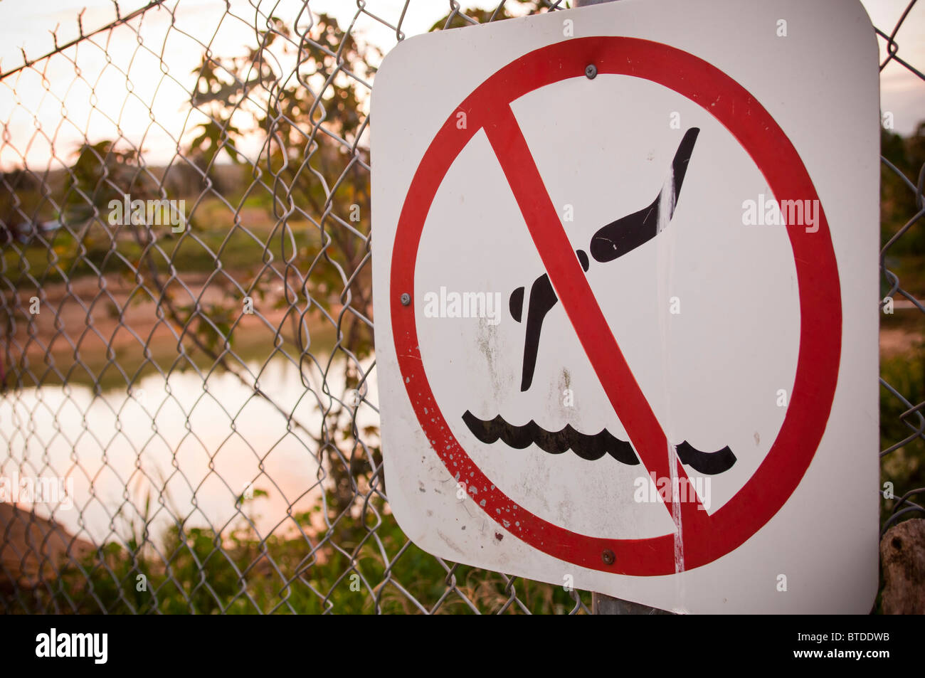 A no swimming warning sign on a fence, with pool behind - Stock Image