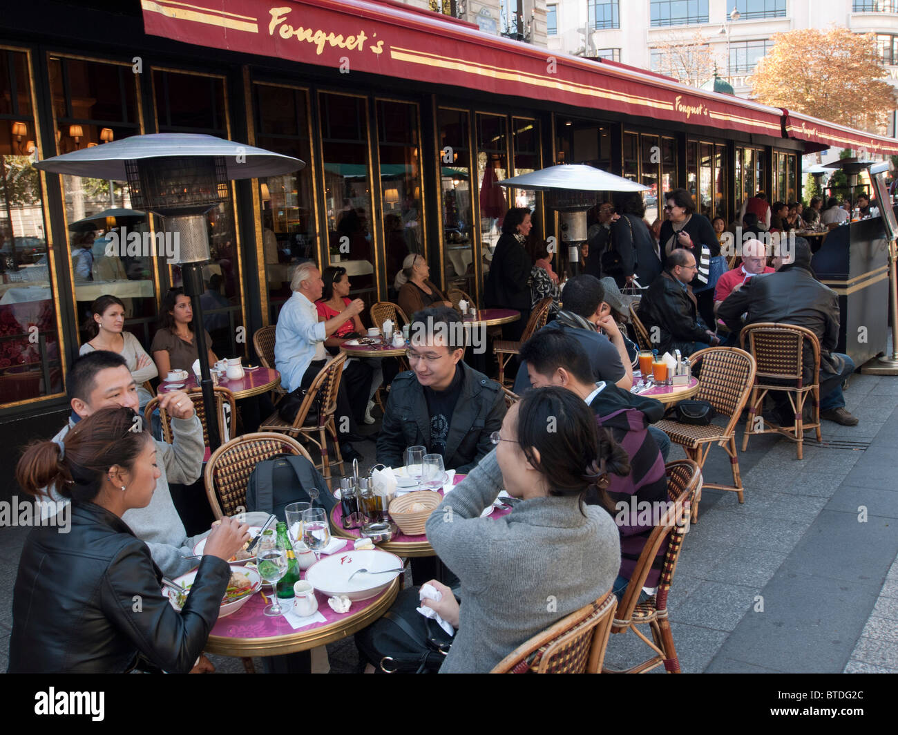 Tourists eating at Fouquet's restaurant on the Champs, Elysees in Paris france - Stock Image