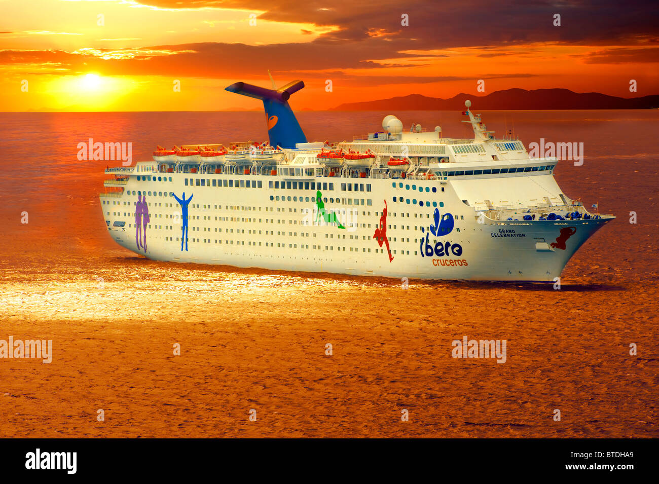 The Iberos Cruise lines Grand Celebration off Mykonos at sunset, Cyclades Islads, Greece - Stock Image